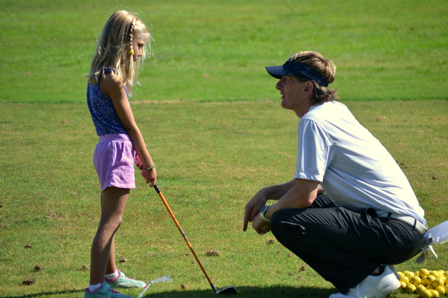 Instructor teaching young girl how to golf