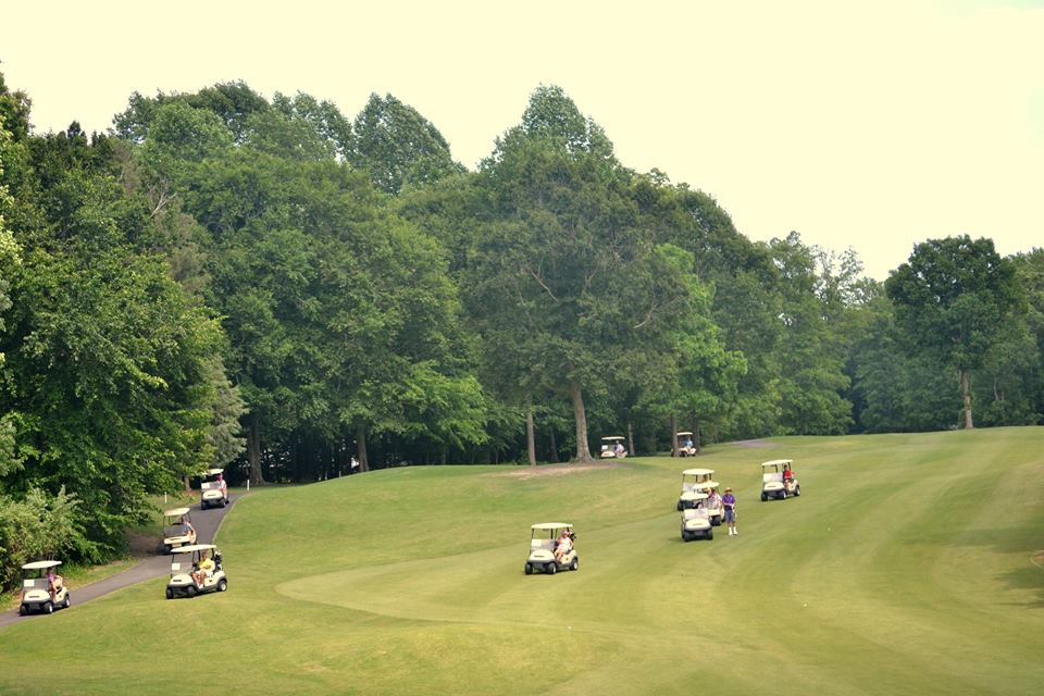 Several carts driving down the fairway
